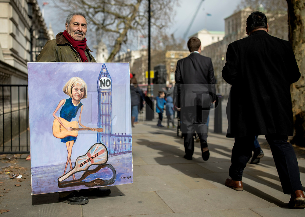 """© Licensed to London News Pictures. 13/03/2019. London, UK. Artist Kaya Mar holds a satirical painting of Prime Minister Theresa May outside Downing Street. MPs will vote on whether to remove the option of a """"no deal"""" departure from the EU today, after Prine Minister Theresa May's proposed deal was defeated for a second time last night. Photo credit: Rob Pinney/LNP"""