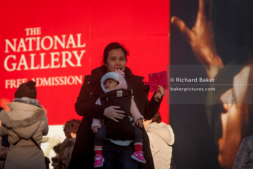 A foreign visitor to London holds her child in front of the National Gallery's construction hoarding featuring their current exhibition about Caravaggio, on 17th January 2017, in Trafalgar Square, London England.