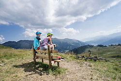 Young couple of mountainbikers sitting on bench in alpine landscape, Zillertal, Tyrol, Austria