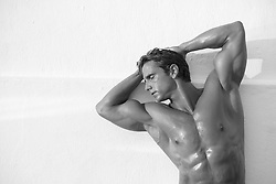 sexy muscular man against a wall with his arms behind his head