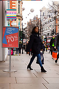 A woman walks past a 70% sale sign outside a branch of Gap in Oxford Street, London, UK on January 03, 2019