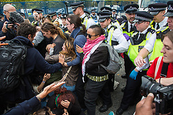 London, UK. 7 September, 2019. Metropolitan Police officers attempt to force back activists blocking the road in front of a truck making a delivery to ExCel London for DSEI, the world's largest arms fair. The sixth day of Stop The Arms Fair protests against DSEI was billed as a Festival of Resistance and included performances, entertainment for children and workshops as well as activities intended to disrupt deliveries to ExCel London for the arms fair.