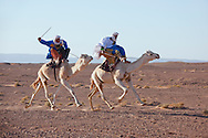 Two nomads on a camel race in the Sahara desert of Morocco.