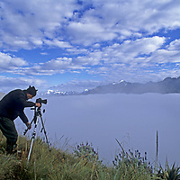 A trekker prepares to photograph fog shrouding the deep canyons and steep ridges of the Cordillera Vilcabamba range of the Peruivian Andes.