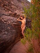 Nude woman posing in a crevice in Leprechaun Canyon, Hanksville, Utah
