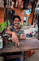 YANGON, MYANMAR - CIRCA DECEMBER 2013: Tailor offering alterations in the street market of Yangon