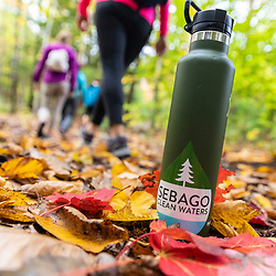 A water bottle and hikers in the Raymond Community Forest in Raymond, Maine. Fall.