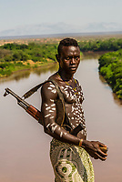 A Kara tribe man holds an AK47 assault rifle, standing with the Omo River behind, Omo Valley, Ethiopia. The tribesman often carry rifles when they herd animals. There are occasionally skirmishes with other tribes over stolen livestock, etc.