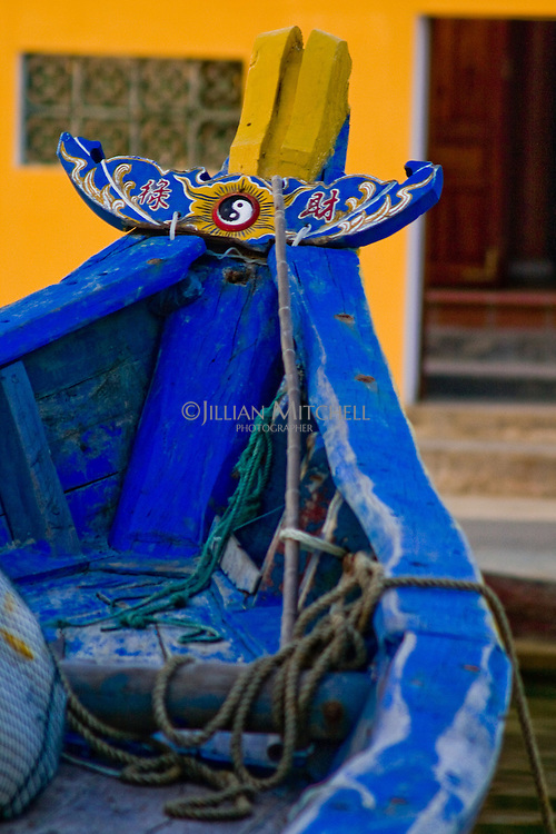 Colourful bow of a wooden boat with Feng shui symbol.