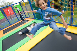 Young boy having fun on a trampoline at a Parklife summer activities event,