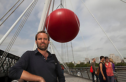 © under license to London News Pictures. 25/06/12. London, UK. New York artist Kurt Perschke's(pictured)  fifteen foot inflatable Red Ball on the Golden Jubilee Bridge, South Bank. It will then move to Waterloo Bridge and Covent Garden...ALEX CHRISTOFIDES/LNP