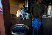 A man dyes cloth blue while a tailor mends clothes behind him, Jaipur, India
