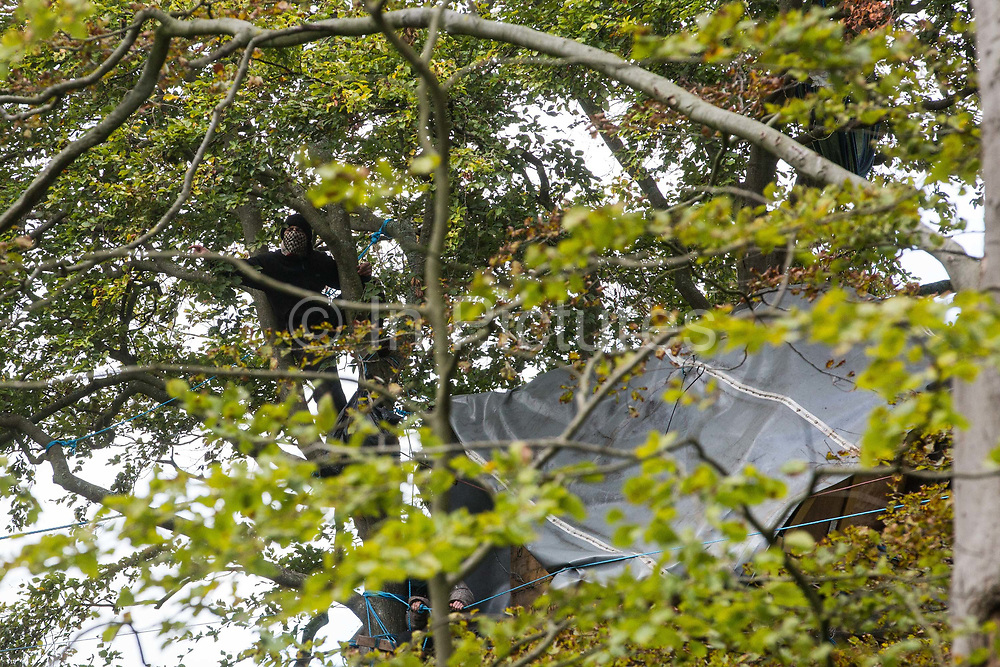 An anti-HS2 tree protector looks down from a tree alongside a makeshift tree house about 60 feet above ground during evictions by National Eviction Team bailiffs working on behalf of HS2 Ltd from a wildlife protection camp in the ancient woodland which inspired Roald Dahl's Fantastic Mr Fox at Jones' Hill Wood on 1 October 2020 in Aylesbury Vale, United Kingdom. Around 40 environmental activists and local residents, some of whom living in tree houses, were present during the evictions at Jones' Hill Wood which had served as one of several protest camps set up along the route of the £106bn HS2 high-speed rail link in order to resist the controversial infrastructure project.