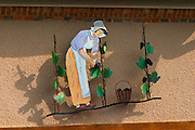 A wrought iron painted sign that illustrates the theme of champagne and wine production: A woman in traditional clothes harvesting grapes, vines and a basket of grapes, the village of Hautvillers in Vallee de la Marne, Champagne, Marne, Ardennes, France