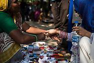Dhaka, Bangladesh - November 1, 2017: A woman shopping for bracelets from a sidewalk vendor tries some on before buying in Dhaka, Bangladesh.