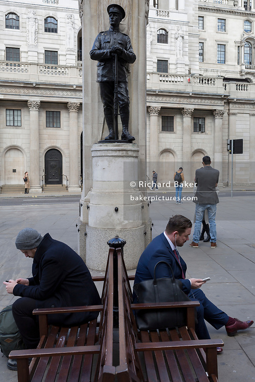 Men use their mobile phones while sitting on the bench beneath the WW1 war memorial opposite the Bank of England in the City of London, the capital's financial district, on 25th March 2019, in London, England.