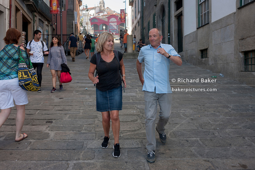 1 of 2 in a sequence showing a husband and wife messing around on a street where they attempt to race backwards on cobbles, on 20th July, in Porto, Portugal. In the first picture we see the man upright and confidently winning the race with the lady - while in the second, he has has fallen over completely, with legs in the air. (Photo by Richard Baker / In Pictures via Getty Images)