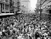 "Y-500609-D46.  Rose Festival crowds at SW 6th & Alder, looking south on 6th.  Pioneer Courthouse on left. June 9, 1950.  Published in Oregonian June 10, 1950: ""Crowds numbering into the thousands swept into the street after the parade passed each of the many blocks along its route. In this view, looking south on Sixth Avenue from Alder street, the massed throngs completely fill the wide street from building to building. This photograph was taken from one of the platforms erected by crews demolishing the old Oregonian building, which has provided vantage points for photographers who covered the Festival parades during their 42-year history."""