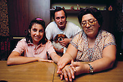 """(1992) Paula Moyano Artiga sits with her grandmother and Uncle Efrain. She was born in captivity and reunited to her family by DNA fingerprinting. Her parents, both """"desaparacidos"""" (disappeared persons, kidnapped and killed by the right-wing Argentine government), are still missing. Buenos Aires, Argentina. DNA Fingerprinting. MODEL RELEASED."""