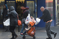 "© Licensed to London News Pictures . 10/12/2014 . Blackpool , UK . Shoppers seek cover in high wind and hail on Bank Hey Street . An explosive cyclogenesis - a fast developing storm in which air pressure falls rapidly - known as a "" weather bomb "" - hits the North of England , bringing storms to the region . Photo credit : Joel Goodman/LNP"