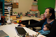 AUSTIN, TEXAS - FEBRUARY 9: Jinny Suh checks her email with her 4-month-old son at her home in Austin, Texas on February 9, 2017. Jinny is a pro-vaccine advocate in addition to running her own businesses from home and raising her two sons. (Photo by Cooper Neill for The Washington Post)
