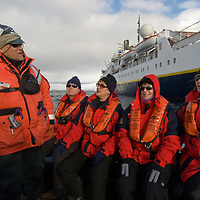 Tourists from the National Geographic Endeavor motor ashore in a zodiac raft to Port Lockroy on Goudier Island, near the Antarctic Peninsula, Antarctica.