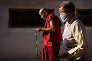 A Buddhist monk and a Tibetan woman wearing a face mask walk, holding prayer beads, around the base of Boudhanath Stupa, Kathmandu, Nepal.