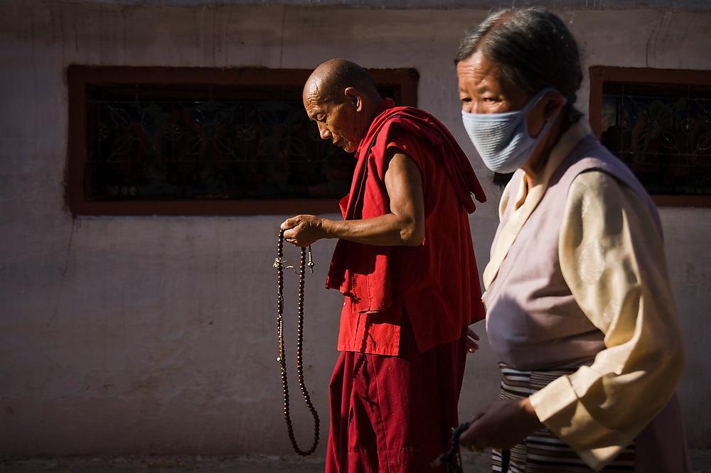 A Buddhist monk and a Tibetan woman wearing a face mask walk, holding prayer beads, around the base of Boudhanath Stupa, Kathmandu, Nepal.