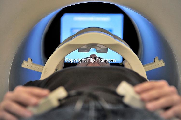 Nederland, Nijmegen, 31-10-2016Bij het FC Donderscentrum van de Radboud universiteit wordt mbv MRI scanner onderzoek gedaan naar de werking van het brein, en processen die zich in de hersenen afspelen. Cognitieve neuroscience. Hierbij wordt samengewerkt door het FC Donderscentrum, het NICI, het umcn en het NCMLS. Een van de doelen is meer inzicht te krijgen in de ziekte van Parkinson. Op de foto is te zien hoe een vrijwilliger in de scanner aktief is bij het kijken naar beelden via spiegels boven zijn ogen.Publicatie geen probleem, persoon is medewerker en heeft toestemming voor publicatie gegeven.Foto: Flip Franssen