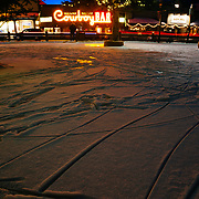 The winter ice rink in downtown Jackson, Wyoming after a snow storm during night time with the Million Dollar Cowboy Bar lighting in the background.