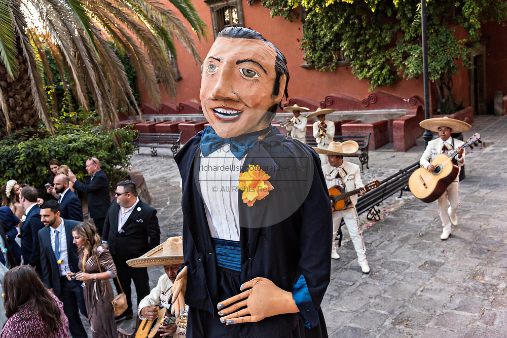A traditional Mexican mariachi band plays as giant puppets called mojigangas dance during a wedding celebration in the Lavaderos del Chorro park in San Miguel de Allende, Guanajuato, Mexico.