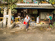 10 NOVEMBER 2014 - SITTWE, MYANMAR: A shop owner throws water into the street in front of his tea shop in Sittwe, Myanmar. Many shop owners throw water on the street to keep the dust down, most of the streets in Sittwe are unpaved. Sittwe is a small town in the Myanmar state of Rakhine, on the Bay of Bengal.    PHOTO BY JACK KURTZ