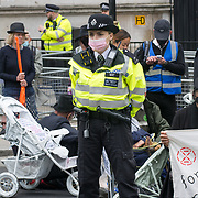 A tiny police woman about 5 foot 2 garding XR Pram Action Aug Rebellion protest in front of 10 Downing Street Slow funeral walk with white painted children's prams – because GOVERNMENT CLIMATE FAILURE IS KILLING CHILDREN. Our Government needs to 'STOP FOSSIL FUEL FUNDING' on 2021-08-31, London, UK.