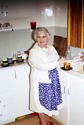 Elderly woman making tea at kitchen sink at home 1970s British way of life