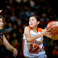 030113  Adron Gardner/Independent<br /> <br /> Gallup Bengal Kaylee Tsinginie (12) drives past Artesia Bulldog Anna Gonzales (33) during the first round of the New Mexico High School State Tournament at Gallup High School Friday.  The Bengals  beat the Bulldogs 71-55 to advance to the second round of the tournament.
