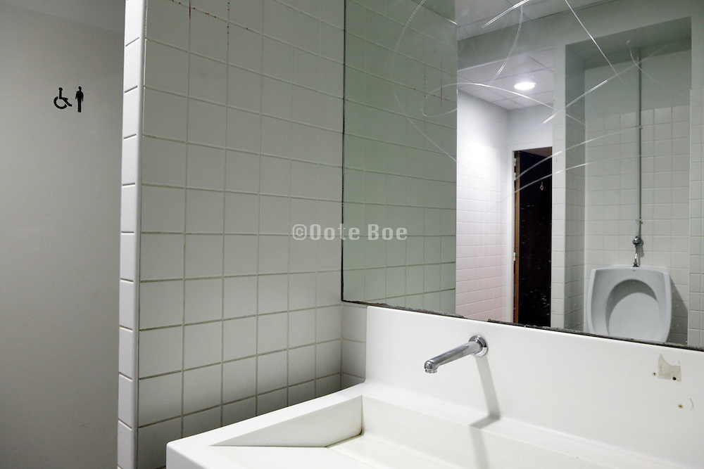 clean white urinal seen in mirror in a for male and handicapped public toilet