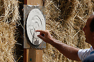 Photo by Andrew Tobin/Tobinators Ltd - 07710 761829 - A judge counts up the score as the peas stick to the plasticine target during the World Peashooting Championships held at Witcham, Cambridgeshire, UK on 13th July 2013. Run in conjunction with the village fair, the Championships have been held in Witcham since 1971 when they were started by a Mr Tyson, the village schoolmaster, in order to raise funds for the village hall.Competitors come from as far afield as the USA and New Zealand to attempt to win the event. The latest technology is often used, including laser sights and titanium and carbon fibre peashooters. All peashooters must conform to strict length rules, not exceeding 12 inches, and have to hit a target 12 feet away. Shooting 5 peas at a plasticine target attached to a hay bale, the highest scorers move through the initial rounds to a knockout competition, followed by a sudden death 10-pea shootout.