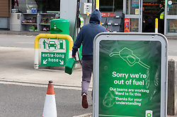 © Licensed to London News Pictures 28/09/2021.<br /> Mottingham, UK, A peron arriving with a jerry can before the tanker has started to pump. A tanker has just delivered fuel to Mottingham BP station in South East London. Within minutes of the tanker arriving motorists started to queue blocking roads. Chaos at the forecourts as people start to panic buy petrol. BP has started to ration petrol and diesel due to a shortage of truckers. Photo credit:Grant Falvey/LNP