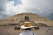 A man wearing a straw hat stands facing the Pyramid of the Sun, or Pyramide del Sol, in the pre-columbian archeological site of Teotihuacan, Mexico state, Mexico, on June 23, 2008. The pyramid measures 738 ft (225 m) across and 246 ft (75 m) high, making it the third largest in the world.