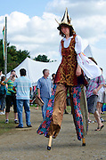 Young woman in costume walking on stilts, Common Ground Fair, Maine