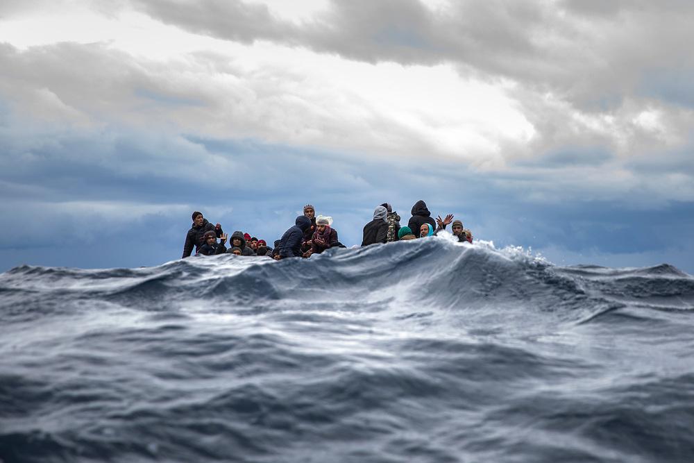Migrantes de Marruecos y Bangladesh reaccionan al ver a un equipo de rescate de la ONG española Open Arms, horas después de haber abandonado Libia para tratar de alcanzar las costas europeas a bordo de un precario bote de madera, mar Mediterráneo central, aguas internacionales, 10 de enero de 2020. (AP Photo / Santi Palacios)