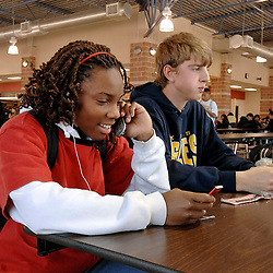 Austin, Texas: January 29, 2007: A ninth-grade student talks on a cellphone and listens to an Apple IPod during lunch hour at Akins High School. The electronic devices are usually not permitted in classrooms.  ©Bob Daemmrich /