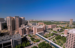 Aerial view of the Texas Medical Center featuring MD Anderson Cancer Center Campus in the foreground with Houston skyline in the distance.