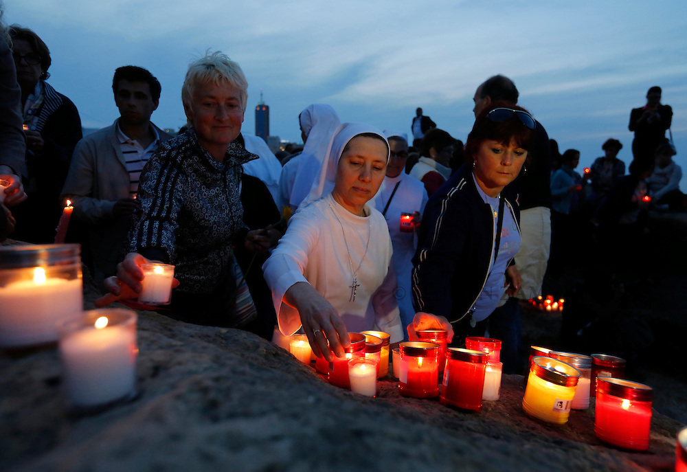 People place candles on the shoreline rocks as they take part in a vigil to commemorate migrants who died at sea in Sliema, outside Valletta, April 22, 2015. European Union leaders who decided last year to halt the rescue of migrants trying to cross the Mediterranean will reverse their decision on Thursday at a summit hastily convened after nearly 2,000 people died at sea.  Public outrage over the deaths peaked this week after up to 900 migrants died last Sunday when their boat sank on its way to Europe from Libya. <br /> REUTERS/Darrin Zammit Lupi MALTA OUT. NO COMMERCIAL OR EDITORIAL SALES IN MALTA