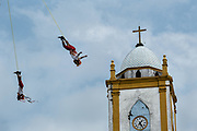 Voladores performs in front of the Church of the Assumption in Papantla, Veracruz, Mexico. The Danza de los Voladores is a indigenous Totonac ceremony involving five participants who climb a thirty-meter pole. Four of these tie ropes around their waists and wind the other end around the top of the pole in order to descend to the ground. The fifth participant stays at the top of the pole, playing a flute and a small drum. The ceremony has been inscribed as a Masterpiece of the Oral and Intangible Heritage of Humanity by UNESCO.