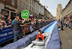 © Licensed to London News Pictures. 04/05/2014; Bristol, UK.  A 90m long slide by artist Luke Jerram on Bristol's Park Street as part of Keep Sunday Special, an idea by Mayor George Ferguson to close off roads in the city centre for street entertainment.<br /> Photo credit: Simon Chapman/LNP