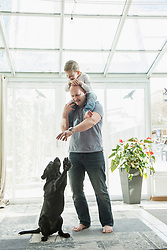 Father playing with dog while carryinng son on his shoulder