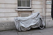 Motorcycle under a cover, parked next to a building. London, UK. Bikes can be parked like this, hiding their number plates and as a result cannot get a parking ticket.