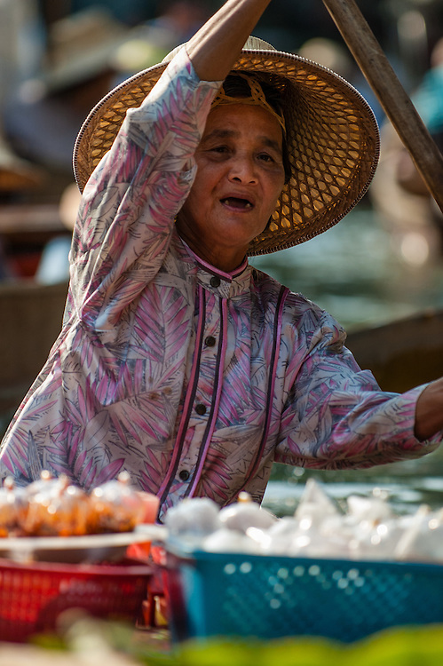 Old woman selling snacks from her canoe at the Floating Market in Damnoensaduak, Thailand. She is a villager selling her wares from a canoe or row boat in the canals west of Bangkok.