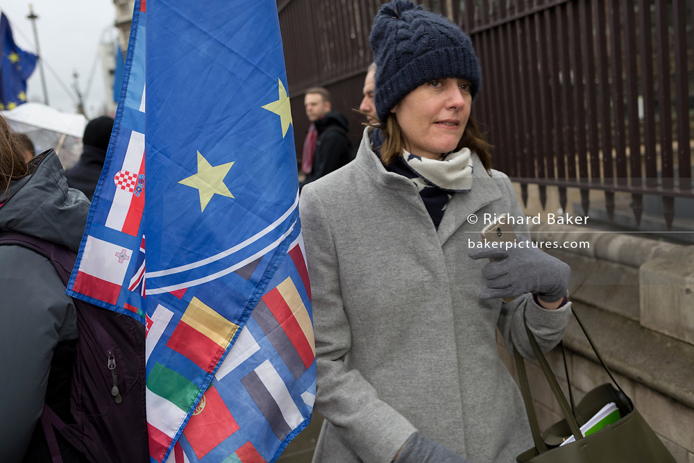 A lady passes the European Union flag while Pro-EU Remainers celebrate EU membership with 'A party like there's no tomorrow' for one last time outside parliament, one day before Brexit Day (the date of 31st January 2020, when the UK legally exits the European Union), in Parliament Square, Westminster, on 30th January 2020, in London, England.